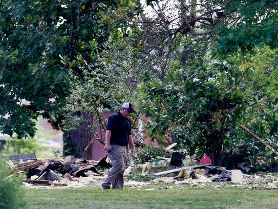 Investigators walk through the scene of a home explosion
