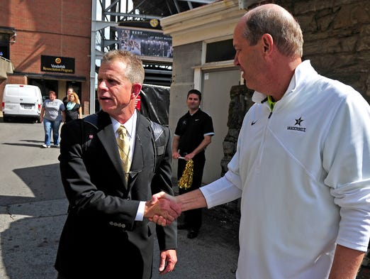 Vanderbilt baseball coach Tim Corbin, left, shakes hands with Vanderbilt basketball coach Kevin Stallings as the baseball team leaves for the College World Series from the campus in Nashville on Wednesday, June 11, 2014.