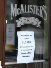 A sign on the front door of McAlister's Deli thanks its customers. The deli has recently closed.
