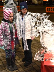 Mikaela Bledsoe, 6, and sister Kailee, 8, check out one of the ice sculptures at Redford's holiday event on Thursday.