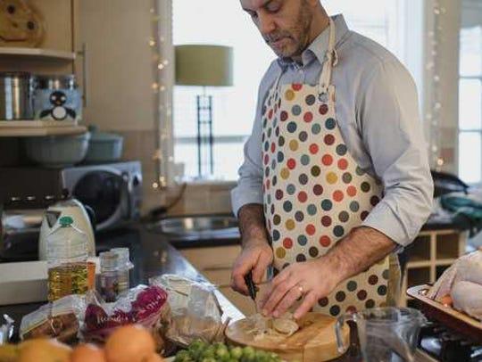 Man in apron preparing food.