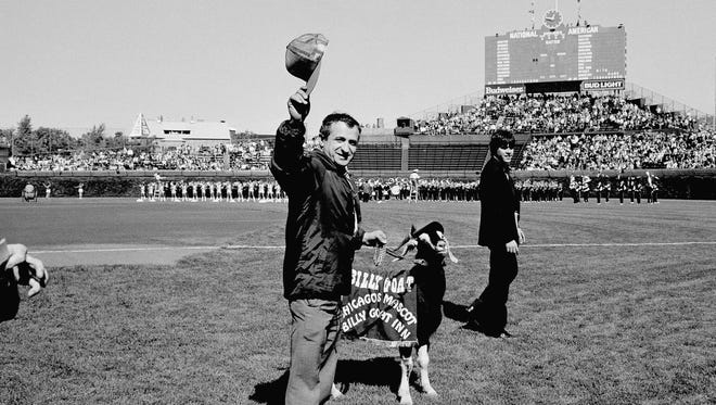 Sam Sianis, owner of the Billy Goat Tavern in Chicago, acknowledges the crowd along with his goat before a National League playoff baseball game between the San Diego Padres and the Chicago Cubs in 1984.