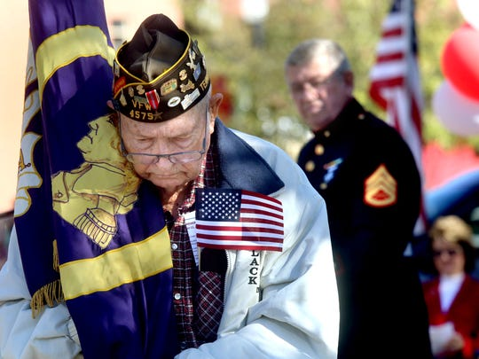 Disabled veteran Frank Hayes, who served in World War II, carries the Purple Heart flag as part of the Veterans Day Memorial Service on the Square in Murfreesboro on Wednesday. Dan Alcorn, United States Marines staff sergeant, Vietnam, 1966-1969, stands in the background.
