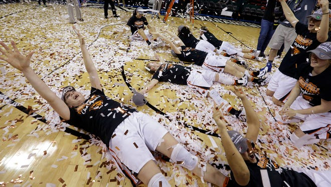 Oregon State players roll in confetti after being awarded the Pac-12 Conference tournament championship trophy after beating UCLA in an NCAA college basketball game, Sunday, March 6, 2016, in Seattle. Oregon State won 69-57.