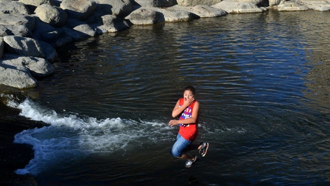 Bryan Cervantes takes a plunge into the Truckee Rive during a spring-like day in downtown Reno on Jan 19, 2015. Warm and dry weather is expected to continue during what is the region's most important month for precipitation.