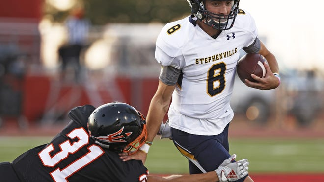 Stephenville's Gavin Rountree (8) breaks away from Dumas' Roberto Rulz (31) during the 46-33 non-district football victory over Dumas Thursday at Pirate Stadium in Lubbock. Rountree had a huge night, passing for four touchdowns and running for two others.