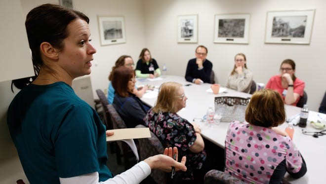 Medical Assistant Jamie Burroughs talks with a team of clinicians that integrate mental health services at a Bellin family practice clinic in Ashwaubenon.
