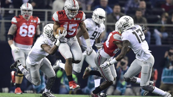 Oregon players try to take down Ohio State's Ezekiel Elliott as the Ducks fall to the Buckeyes in College Football Playoff Championship at AT&T Stadium Monday, Jan. 12, 2015, in Arlington, Texas.
