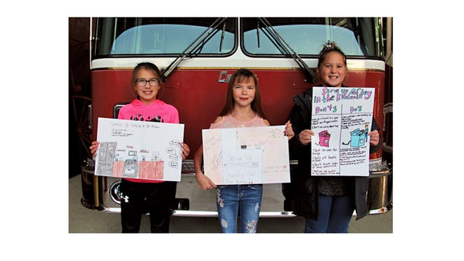 """Winners of the Sleepy Eye Fire Department's fifth grade Fire Prevention Week poster contest displayed their posters, depicting the theme, """"Serve Up Fire Safety in the Kitchen"""" The young artists received cash prizes for their winning effort, from left: Karly Wendinger, Kelsey Ladd, and Kenley Jensen. The girls are students at Sleepy Eye Elementary School."""