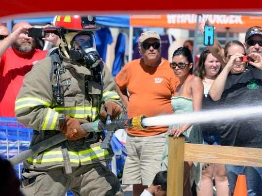 Firefighters compete against the clock Saturday during the Beach Firefighter Challenge at Pensacola Beach.