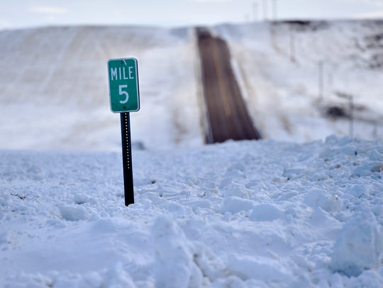 A mile marker is buried north of Cut Bank Wednesday. Snow and wind has made roads impassable at times making it difficult for ranchers to reach cattle.