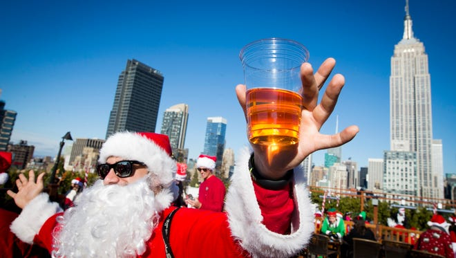 A man dressed as Santa Claus holds a beer as he and others participate in SantaCon on a rooftop bar Saturday. (AP Photo/John Minchillo)