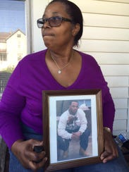 Lillian Webb holds a photo of her son, Myron Webb.