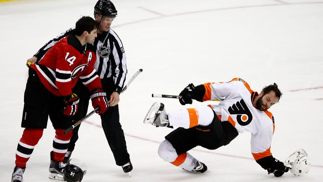 Flyers defenseman Radko Gudas, right, falls down after being pushed by Devils center Adam Henrique, left, as linesman David Brisebois (96) intervenes Thursday, Dec. 22, 2016, in Newark. The Devils won 4-0. The Devils and the Flyers meet again Saturday,