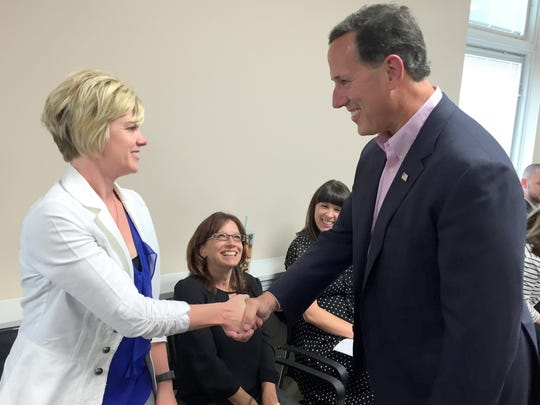 Rick Santorum greets Amy Reineke, a employee of Cambridge Investment Research, during a visit Thursday to the company's offices in Fairfield, Iowa.