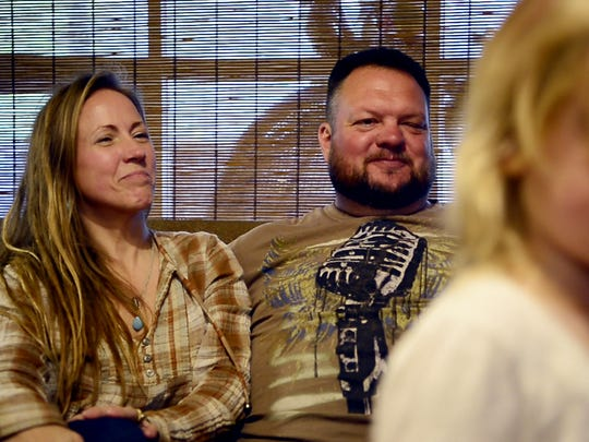 Amy and Kevin smile fondly at their daughter, Emma, while she talks about gender at their home in Arden.