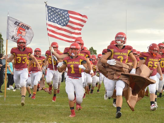 The Elgin Comets run onto the field before the start of the game with Riverside while wearing their tribute uniforms to the Oorang Indians, a former NFL team based in nearby LaRue in the early 1920s.