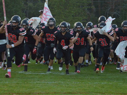 Pleasant's football team runs onto the field this season. The Spartans finished as Division V regional runners-up.