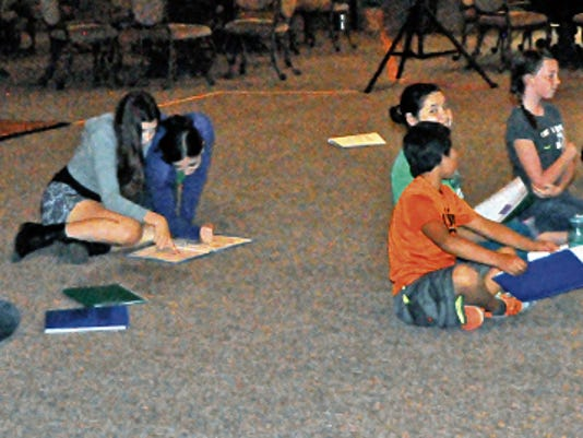 """Children learn lines while waiting for their turn to go on the stage during """"Aladdin"""" rehearsals at Mountain Annies."""