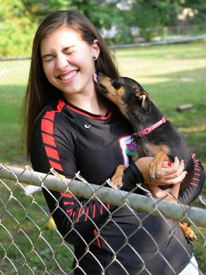 Seneca High School senior Cassidie Cartwright gets an affectionate lick from Bella, one of her two dogs (The other, not shown, is Chewy.) Sept. 2, 2015