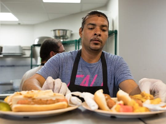 Tacos not Bombs member Jose Rodriguez plates food during lunch service Saturday, May 27, 2017, at Metro Ministries.