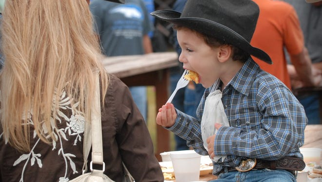 Austin D'Elia, 3 (from right) takes a bite of his eggs at the Ranch Hand Breakfast with his parents, Joe and Jennifer D'Elia, in 2014 at King Ranch.