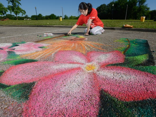 Jenny Baek works on the Baldwin Jr. High entry in the chalk art competition at the Flimp Festival at the Montgomery Museum of Fine Arts in Montgomery, Ala., on Saturday morning May 2, 2015.