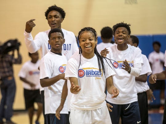 Narla Jordan, 18 of Detroit, center, runs drills with Detroit Pistons Stanley Johnson (far left) and their group during the Building Bridges through Basketball program at  S.A.Y. Detroit Play Center in Detroit Mich., Wednesday, October 11, 2017.