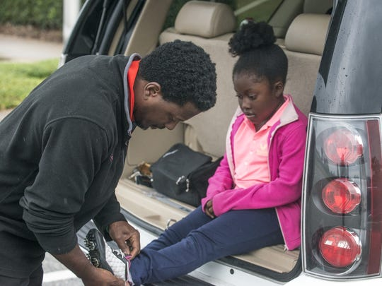Lauryn Olivia Leonard, 8, of Montgomery gets help with her golf shoes from dad, Quincy Leonard, at Gateway Park in Montgomery on Monday, Sept. 21, 2015. Lauryn won  the Regional Final qualifying round for girls 7-9 at Valhalla Golf Club on Sept. 12, 2015, in Louisville, Kentucky. She is one of the of nation's few to make cut for the Drive, Chip and Putt Championship on April 2016 at Augusta National Golf Club in Augusta, Georgia.