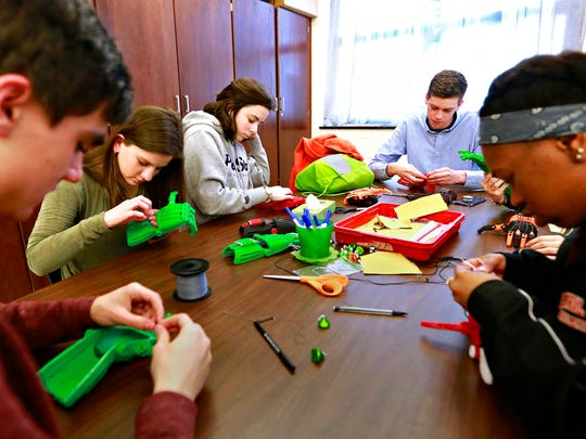 Central York's e-NABLE club members, from left, Adam Rilatt, 16, Mikella Wisler, 17, Renee Rambler, 17, Patrick O'Neill, 16, Rachel Rambler, 17, and Shannon Salandy, 17,  assemble prosthetic hands made with a 3-D printer at Central York High School in Springettsbury Township, Friday, Feb. 9, 2018. Dawn J. Sagert photo