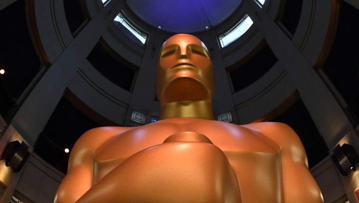 Oscar statues stand at the end of the red carpet arrivals