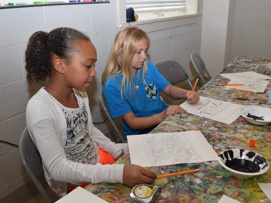 Alexis Orphey (left) and Zoe Nichols draw designs for an art class taught by Pat Phillips at a summer art camp held at River Oaks Art Center Tuesday.