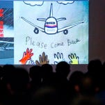 Photos and art works bringing prayers for Malaysia Airlines Flight 370 are projected on a screen before a briefing meeting between Malaysian officials and relatives of Chinese passengers onboard Malaysia Airlines Flight 370 at a hotel in Beijing, China, Saturday, March 29, 2014. No debris spotted in an area off the west coast of Australia has been recovered, a Malaysian minister involved in the search for Malaysia Airlines Flight 370 said Saturday, adding he hoped for some news soon. (AP Photo/Alexander F. Yuan)