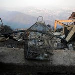 A group of firefighters try to extinguish the flames as a forest fire rages towards urban areas in Valparaiso, Chile, Sunday April 13, 2014. Authorities say the fires have destroyed hundreds of homes, forced the evacuation of thousands and claimed the lives of at least seven people.  ( AP Photo/ Luis Hidalgo)