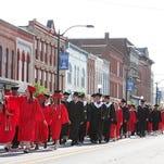 Marshall High School seniors parade through downtown Marshall before their graduation ceremony Saturday evening.