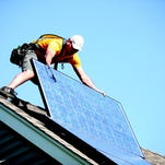 A Vivant Solar installer places a piece of the solar array on a home.