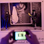 A visitor takes a picture of a 1968 Michael Cooper photo of Rolling Stones frontman Mick Jagger and guitarist Keith Richards. Cooper was the official photographer of the Rolling Stones in the first years of the band.