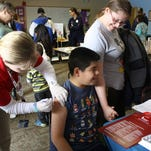 Cristian Hernandez, 10, receives a flu shot from Hannah Raake as his mother, Sanjuana Hernandez, holds his hand during the seventh annual St. Mark's Neighborhood Health Fair in New Albany on Saturday. (By Jenna Esarey, special to The Courier-Journal) February 28, 2015.