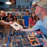 Mark Ertter, left, hands an album to Mark Brace on a recent Record Store Day at Main Street Music in Philadelphia.