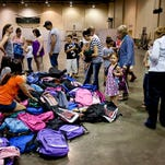 Students pick out their backpacks with supplies during a free backpack giveaway Wednesday in Port Huron by the Community Foundation of St. Clair County.