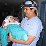 Dr. Andres Herrera holds a child with a cleft lip while another rests in the make-shift operating room in Puno, Peru.