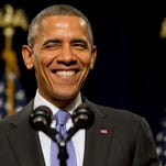 President Barack Obama winks as he is welcomed before speaking to House Democrats in Cambridge.