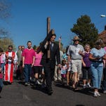 LDS Stake President Donald Lyman carries a cross along Diagonal Street in 2013. Community faith leaders and several hundred residents are expected to commemorate Good Friday by participating in Stations of the Cross starting at Bluff Street Park and ending at the St. George Catholic Church starting at 11 a.m. Friday