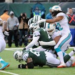 Rookie quarterback Geno Smith, center left, is sacked by Miami Dolphins defensive end Olivier Vernon during the first half last Sunday. The Jets have not scored a touchdown since Nov. 17.