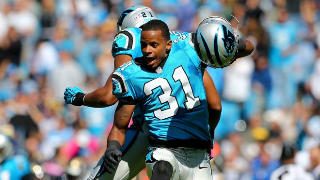 James Dockery of the Carolina Panthers celebrates with a teammate during a game on Oct. 20, 2013.