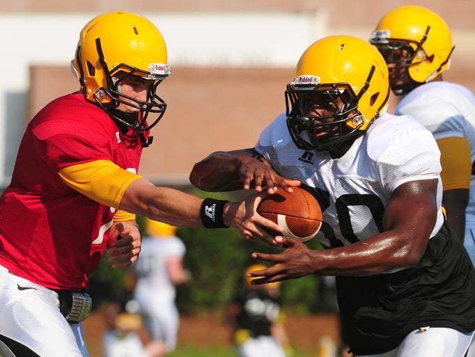 Southern Miss Quarterback Nick Mullens (9) drops back to hand off the ball to running back Jalen Richard (30) during a football practice Tuesday morning at Joe P. Park Practice Facility.