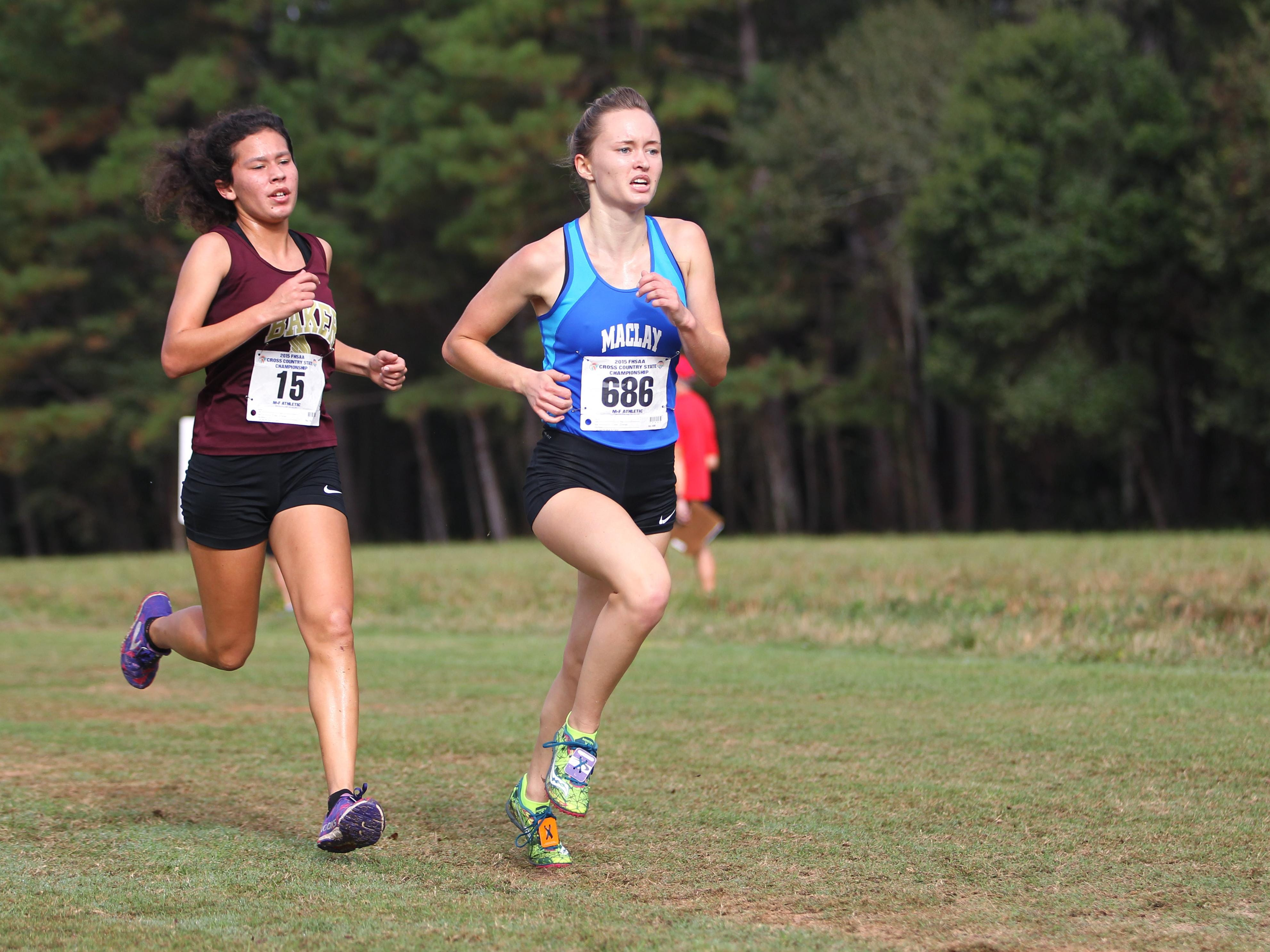 Maclay junior Caroline Willis (right) battles Baker freshman Maya Espinosa during Saturday's 1A race at the FHSAA cross country finals at Apalachee Regional Park. Willis finished in the top 10 and the Marauders were the 1A runner-up.