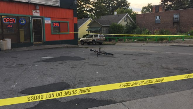 A bike sits behind the crime scene tape in front of 857 Portland Ave. where an 18-year-old city resident was shot on Aug. 13.