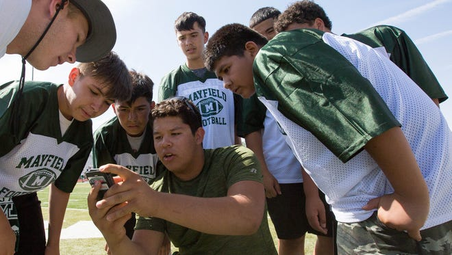 Alfonzo Figuerro, 18, a Mayfield football player gathers football campers around him to talk strategy and what play they will run during their 7 on 7 tournament at the Field of Dreams Thursday during Mayfield football's Jim Bradley Camp for Champs.