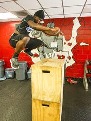 Zaquandre White works out in the weight room of the
